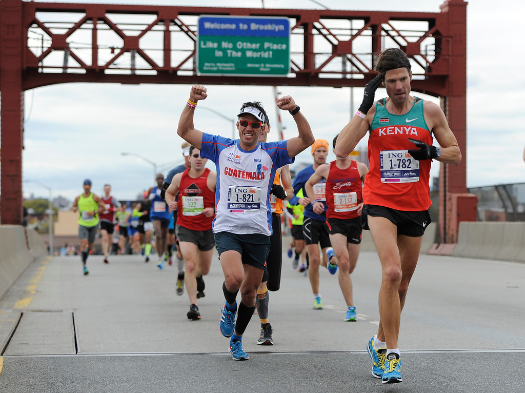 Description of . A runner celebrates as he crosses the Pulaski Bridge into the Queens borough of New York during the New York City Marathon on Sunday, Nov. 3, 2013. New York. (AP Photo/Kathy Kmonicek)