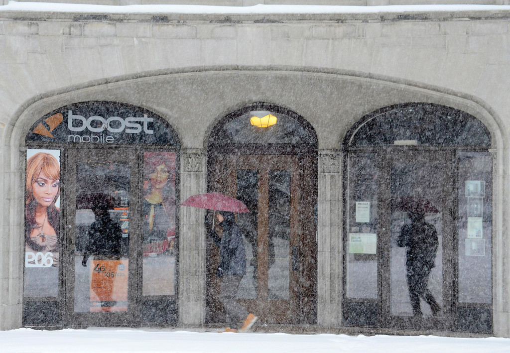 Description of . A pedestrian passes a North Street storefront as snow falls in Pittsfield, Mass., Wednesday Feb 5, 2014. The storm is expected to drop a foot or more of snow on some areas of the state. (AP Photo/The Berkshire Eagle, Ben Garver)