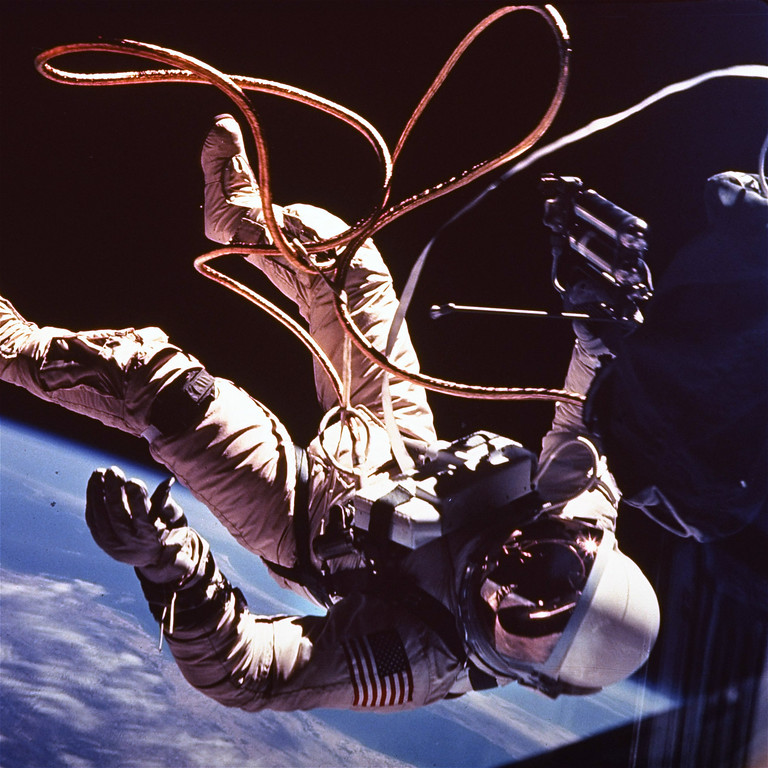Description of . Astronaut Ed White moves away from his Gemini 4 capsule as his golden tether unreels from a black bag in which it was kept until he emerged from the spacecraft.  He somersaulted away for most of the tether's length, then maneuvered back with the aid of an oxygen rocket gun.  This picture was made by White's fellow astronaut, James McDivitt, June 8, 1965, with a Hasselblad camera. (AP Photo/NASA)