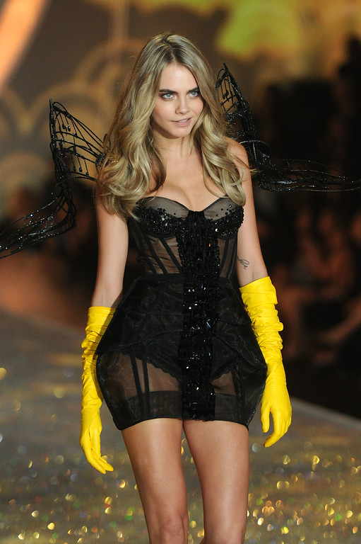 Description of . Model Cara Delevingne walks the runway at the 2013 Victoria's Secret Fashion Show at Lexington Avenue Armory on November 13, 2013 in New York City.  (Photo by Jamie McCarthy/Getty Images)