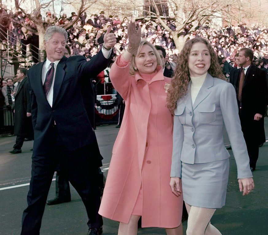 Description of . President Clinton, Mrs. Clinton and daughter Chelsea wave as they walk down Pennsylvania Avenue, Monday Jan. 20, 1997 to start the presidential inaugural parade. (AP Photo/Greg Gibson)