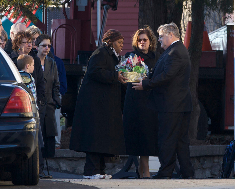 Description of . A woman delivers flowers to the Munson-Lovetere funeral home during the wake of school principal Dawn Hochsprung, a victim in the Sandy Hook Elementary School shooting, in Woodbury, Connecticut, December 19, 2012. Six more victims of the Newtown school shooting will be honored at funerals and remembrances on Wednesday, including the school principal who was killed with 20 of her students and five other staff members at the Sandy Hook Elementary School. REUTERS/ Michelle McLoughlin