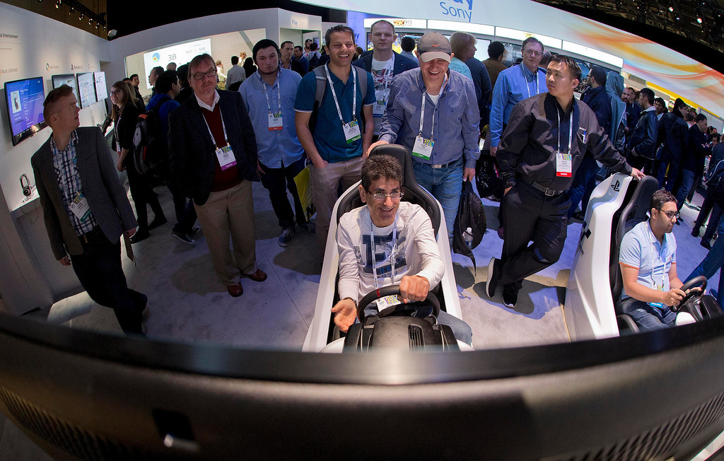 Description of . Trade show attendees play with the Sony PlayStation Gran Turismo driving simulator at the International Consumer Electronics Show, Wednesday, Jan. 8, 2014, in Las Vegas. (AP Photo/Julie Jacobson)