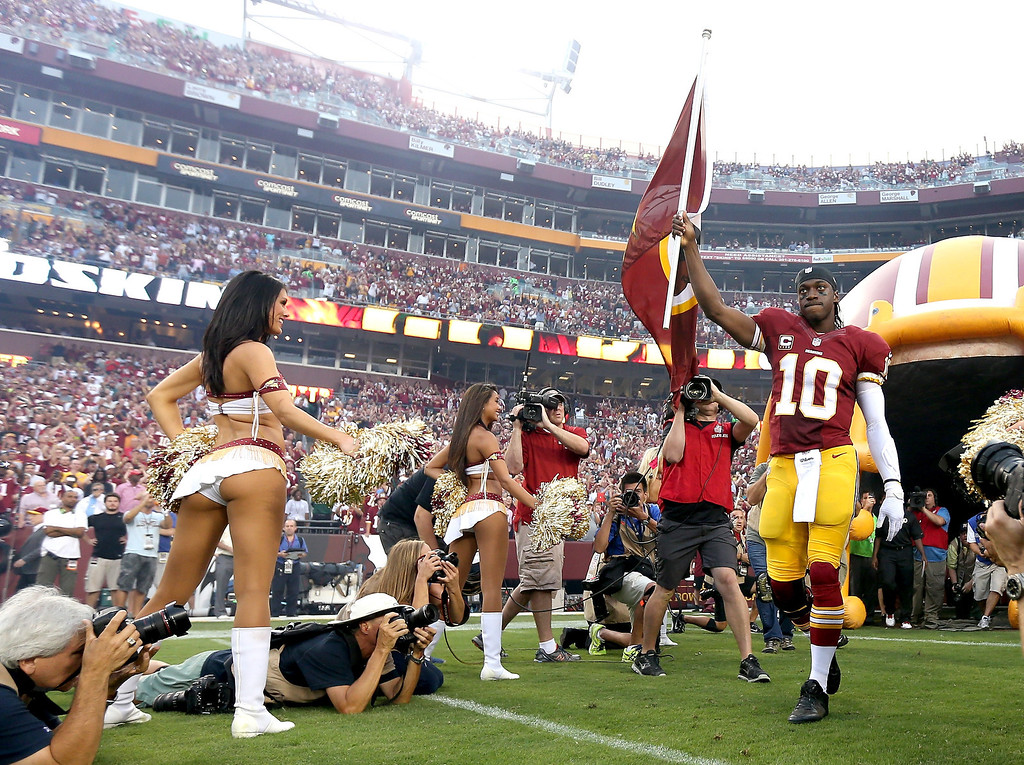 Description of . Puarterback Robert Griffin III #10 of the Washington Redskins leads the team out onto the field before taking on the Philadelphia Eagles at FedExField on September 9, 2013 in Landover, Maryland.  (Photo by Rob Carr/Getty Images)