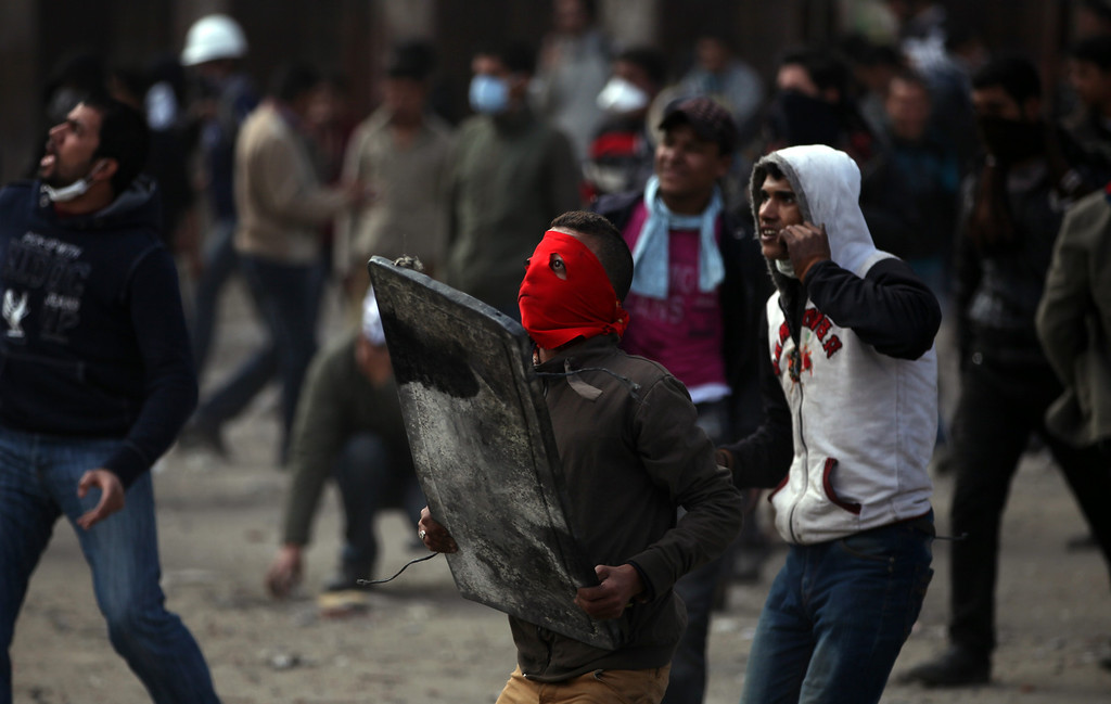 . Egyptian protesters throw stones at riot police, not seen, and use scrap metal to deflect stones being returned by security forces during clashes near Tahrir Square, Cairo, Egypt, Friday, Jan. 25, 2013. Youth activists and opposition groups have called for large rallies to mark the second anniversary of Egypt\'s Jan. 25, 2011 uprising that toppled long-time authoritarian leader President Hosni Mubarak. (AP Photo/Khalil Hamra)