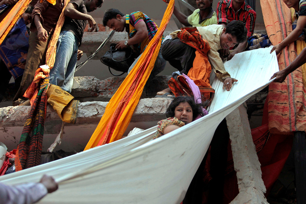 Description of . Rescue workers use pieces of clothes to bring down a survivor after an eight-story building housing several garment factories collapsed in Savar, near Dhaka, Bangladesh, Wednesday, April 24, 2013.  (AP Photo/ A.M. Ahad)