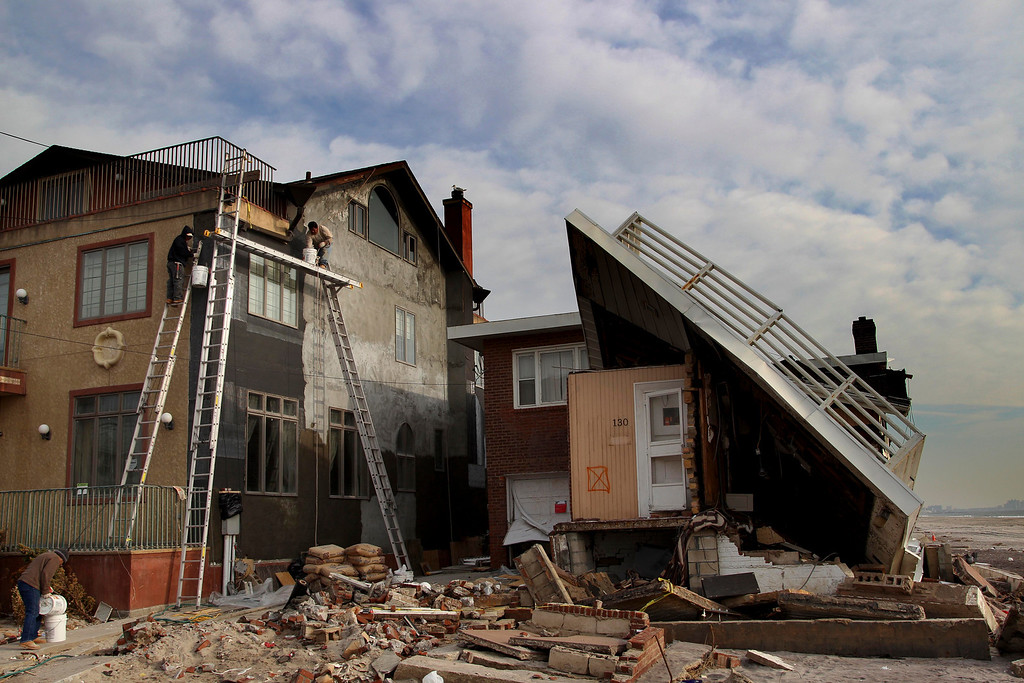Description of . Men repair a home damaged by Superstorm Sandy next to a one that is almost collapsed on the Rockaway Peninsula in New York, Thursday, Nov. 29, 2012.  Sandy damaged or destroyed  305,000 housing units in New York.  (AP Photo/Seth Wenig)