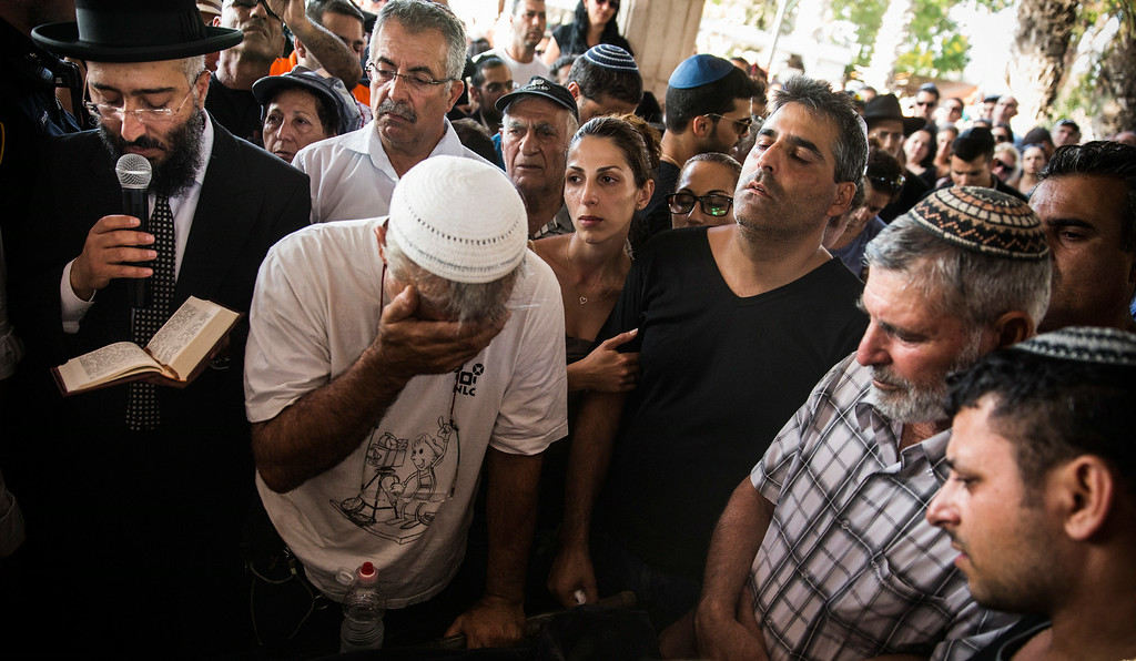 Description of . People mourn during the funeral of Dror Khenin at a cemetary on July 16, 2014 in Yahud Monoson, Israel. Yesterday Khenin was the first Israeli to be killed by a Hamas mortar as he offered food to Israeli soldiers working near the Erez border crossing between Israel and Gaza. As Operation
