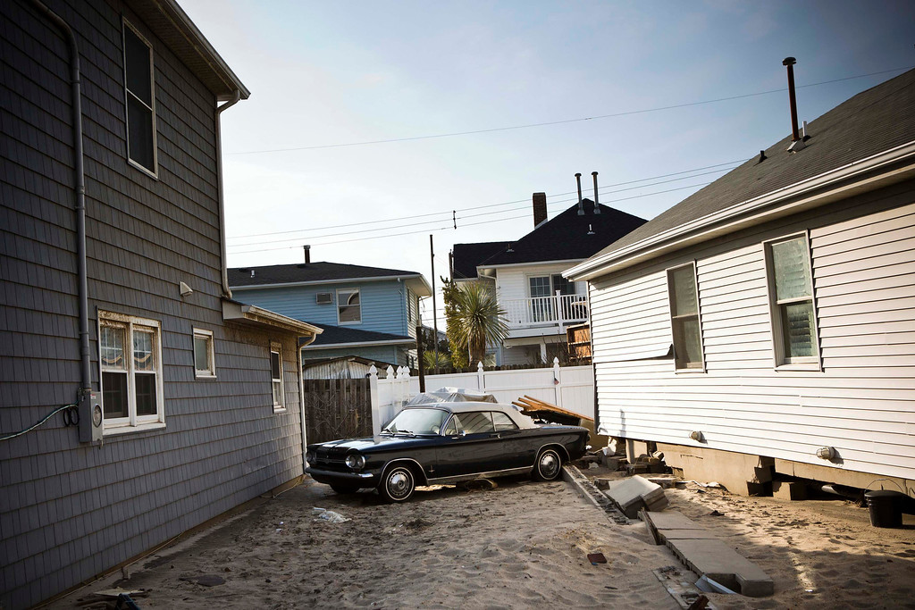 Description of . A vintage car is seen between two houses in the Ortley Beach area of Toms River, New Jersey, which was heavily damaged by Hurricane Sandy, November 28, 2012. The storm made landfall along the New Jersey coastline on October 29. REUTERS/Andrew Burton