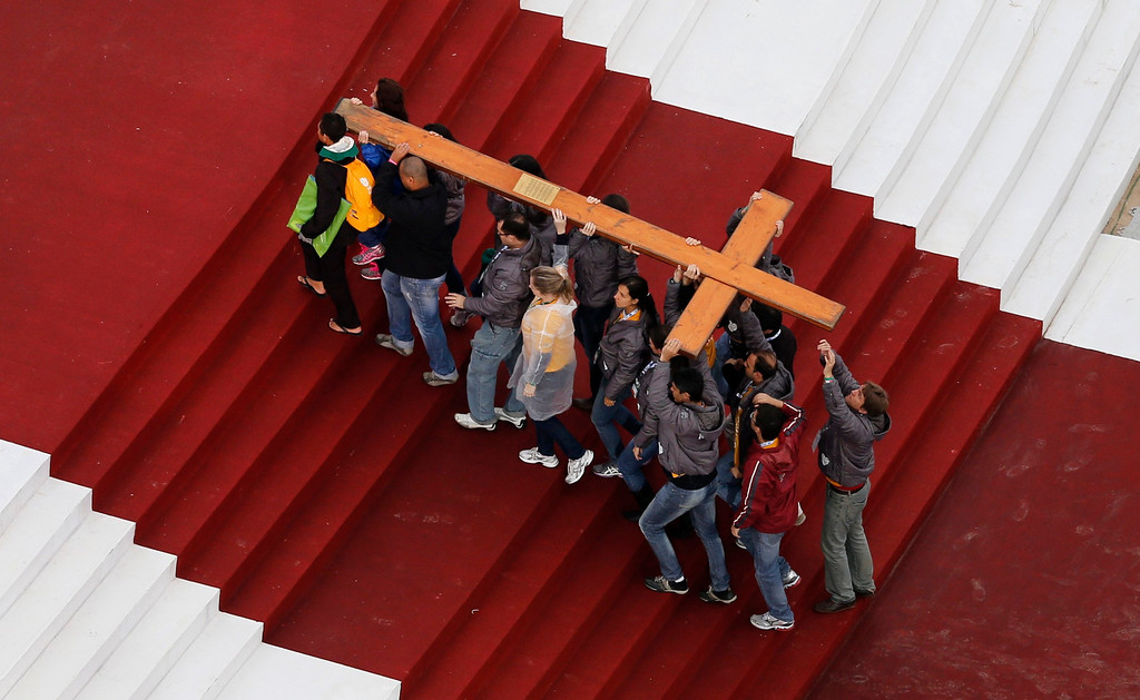 Description of . Catholic pilgrims carry the World Youth Day Cross up to a stage before the arrival of Pope Francis on Copacabana beach in Rio de Janeiro July 25, 2013. Pope Francis is on the fourth day of his week-long visit for World Youth Day.          REUTERS/Sergio Moraes