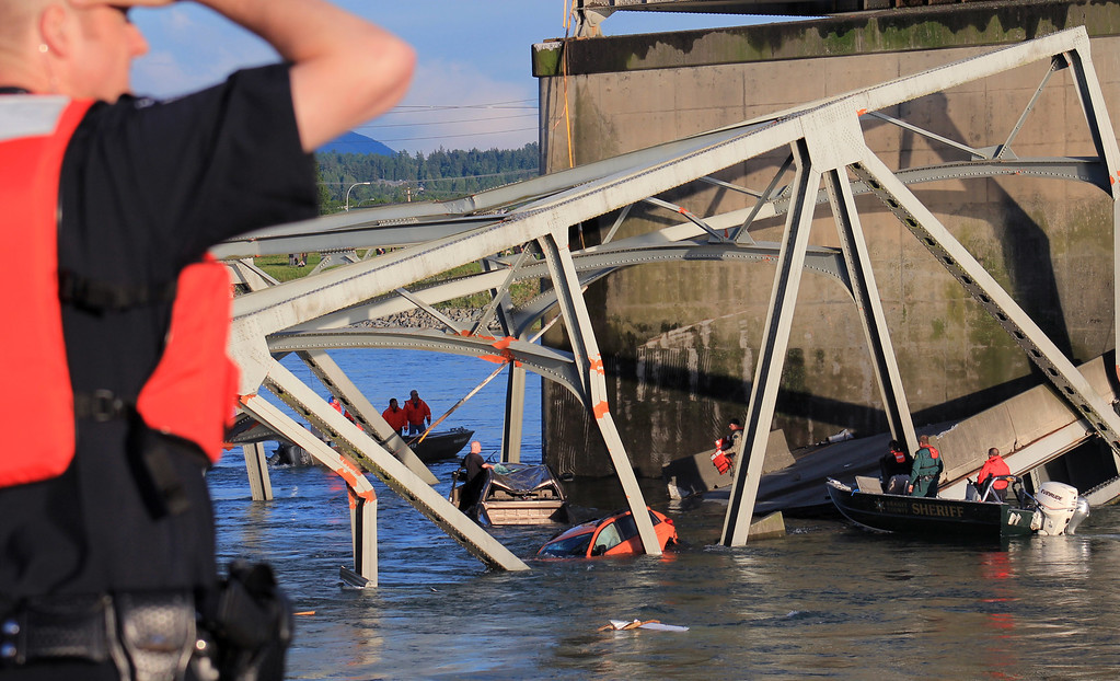 Description of . In this photo provided by Francisco Rodriguez, rescue boats approach victims at their vehicles in the Skagit River after the collapse of the Interstate 5 bridge there minutes earlier Thursday, May 23, 2013, in Mount Vernon, Wash. (AP Photo/Francisco Rodriguez)