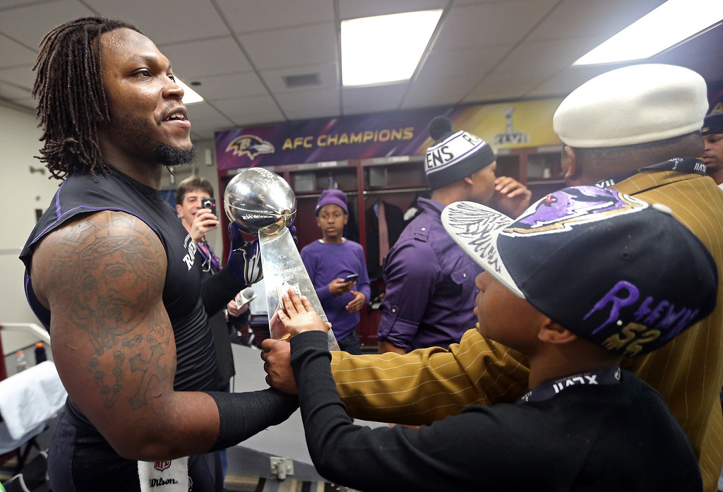 Description of . Courtney Upshaw #91 of the Baltimore Ravens holds the Vince Lombardi Trophy in the locker room after defeating the San Francisco 49ers during Super Bowl XLVII at the Mercedes-Benz Superdome on February 3, 2013 in New Orleans, Louisiana. The Ravens defeated the 49ers 34-31. (Photo by Chris Graythen/Getty Images)
