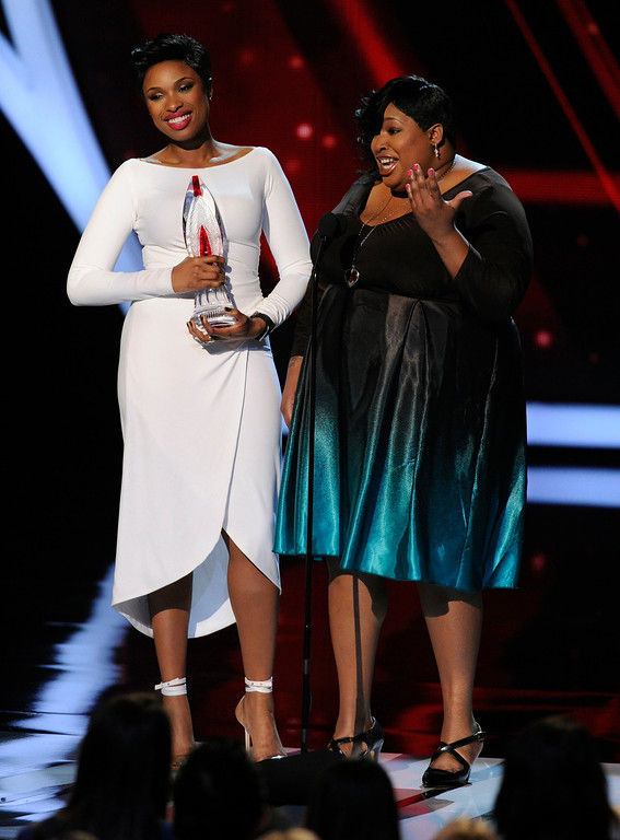 Description of . RETRANSMISSION TO CORRECT THAT ONLY JENNIFER HUDSON WON THE AWARD - Jennifer Hudson, left, accepts the favorite humanitarian award as her sister Julia Hudson looks on, at the 40th annual People's Choice Awards at the Nokia Theatre L.A. Live on Wednesday, Jan. 8, 2014, in Los Angeles.(Photo by Chris Pizzello/Invision/AP)
