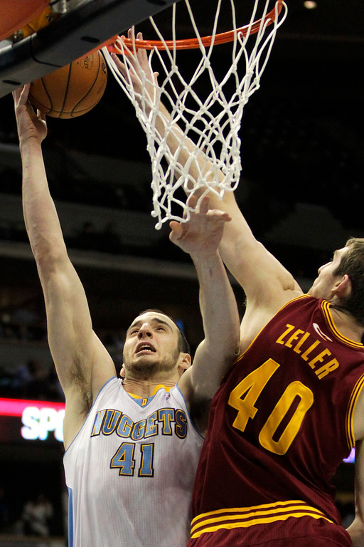 Description of . Denver Nuggets's Kosta Koufos (41) heads to the basket against Cleveland Cavaliers' Tyler Zeller (40) during the first quarter of an NBA basketball game Friday, Jan. 11, 2013, in Denver. Koufos scored a career high of 21 points helping the Nuggets win 98-91. (AP Photo/Barry Gutierrez)