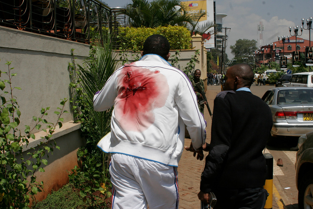 Description of . A wounded man is escorted outside the Westgate Mall, an upscale shopping mall  in Nairobi, Kenya Saturday Sept. 21 2013, where shooting erupted when armed men attempted to rob a shop, according to police.  (AP Photo/Sayyid Azim)