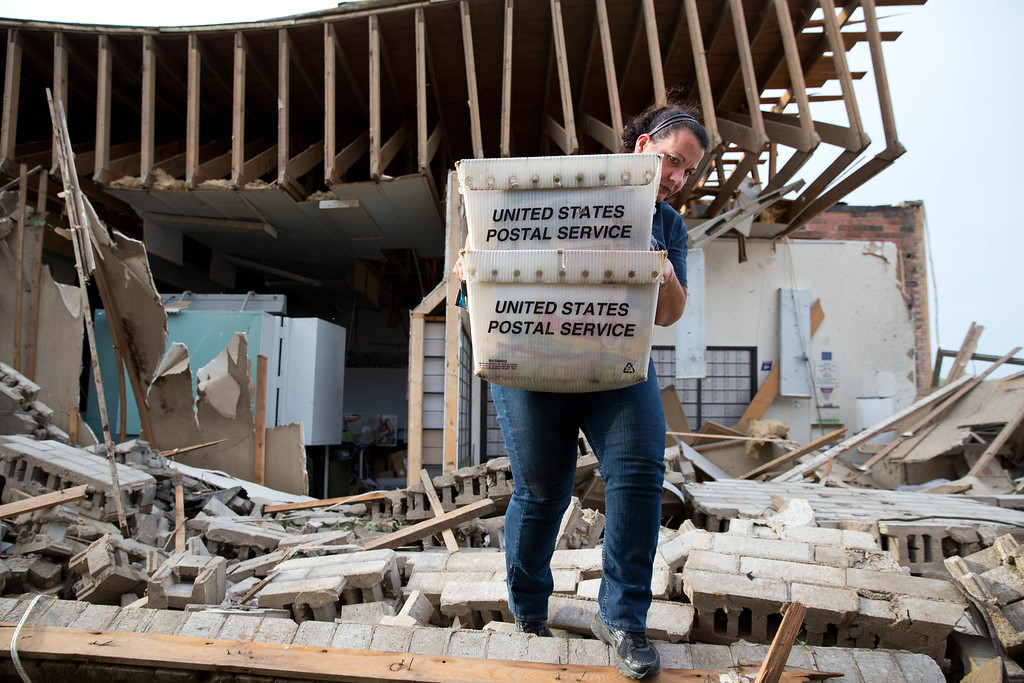 Description of . Darcy Kleinschmit, left, a rural mail carrier from Norfolk, helps save the mail from the destroyed Pilger Post Office on Monday, June 16, 2014 in Pilger, Neb.  The National Weather Service says the storm that struck northeast Nebraska appears to have produced four tornadoes, one of which ravaged the town of Pilger.   (AP Photo/The World-Herald, Ryan Soderlin)