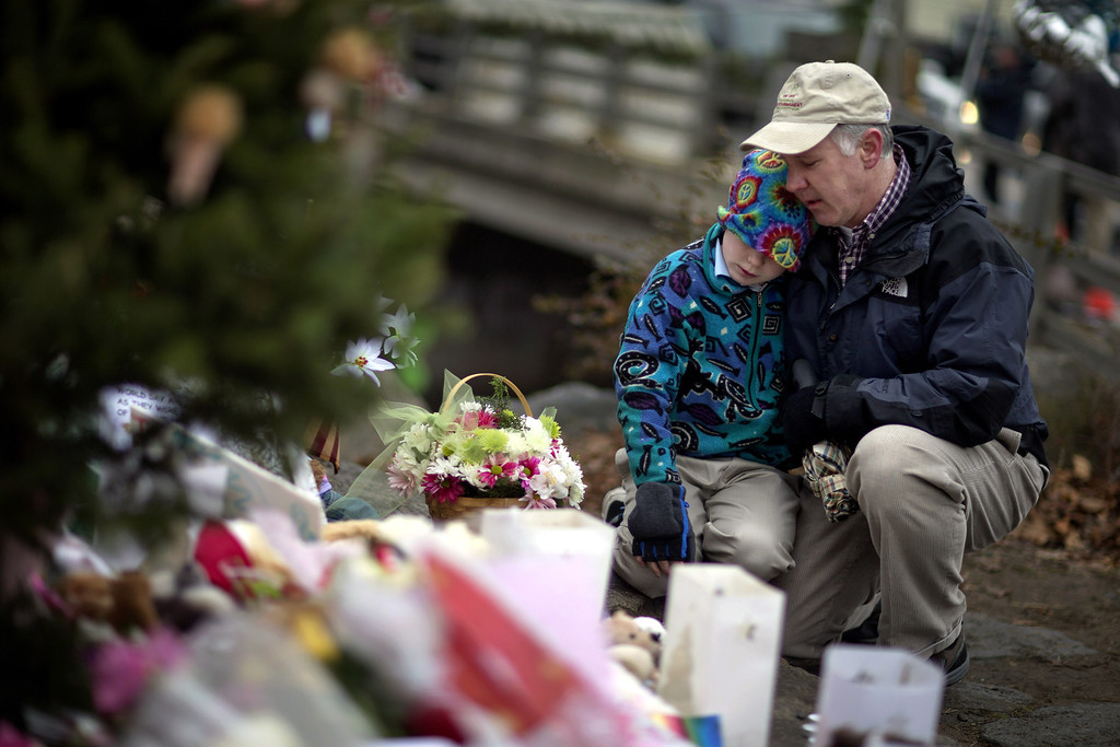 Description of . David Freedman, right, kneels with his son Zachary, 9, both of Newtown, Conn., as they visit a sidewalk memorial for the Sandy Hook Elementary School shooting victims, Sunday, Dec. 16, 2012, in Newtown, Conn. A gunman walked into Sandy Hook Elementary School in Newtown Friday and opened fire, killing 26 people, including 20 children. (AP Photo/David Goldman)