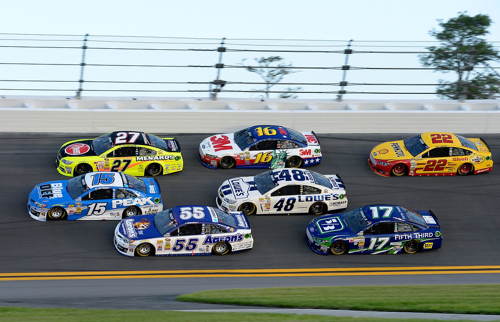 Description of . DAYTONA BEACH, FL - JULY 06:  (L-R) Clint Bowyer, driver of the #15 Blue DEF Diesel Exhaust Fluid Toyota, Paul Menard, driver of the #27 Rheem / Menard\'s Chevrolet, Michael Waltrip, driver of the #55 Aaron\'s Dream Machine Toyota, Greg Biffle, driver of the #16 3M Ford, Jimmie Johnson, driver of the #48 Lowe\'s Dover White Chevrolet, Ricky Stenhouse Jr., driver of the #17 Fifth Third Ford, and Joey Logano, driver of the #22 Shell Pennzoil Ford, race three wide during the NASCAR Sprint Cup Series Coke Zero 400 at Daytona International Speedway on July 6, 2013 in Daytona Beach, Florida.  (Photo by John Harrelson/Getty Images)