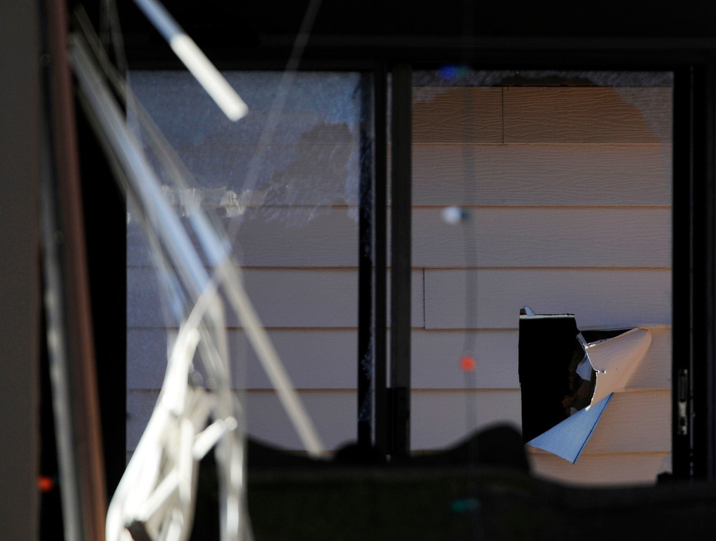 Description of . A hole was torn into the wall in a garage behind the town home at 16005 Ithaca Place in Aurora Saturday afternoon. The bodies of four people, including a gunman are dead at the scene following a standoff situation early Saturday morning. The Denver Post/ Andy Cross
