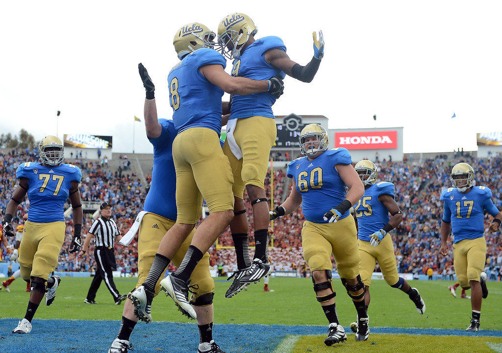 Description of . Joseph Fauria #8 of the UCLA Bruins celebrates his touchdown with Jerry Johnson #9 for a 17-0 lead over the USC Trojans at Rose Bowl on November 17, 2012 in Pasadena, California.  (Photo by Harry How/Getty Images)