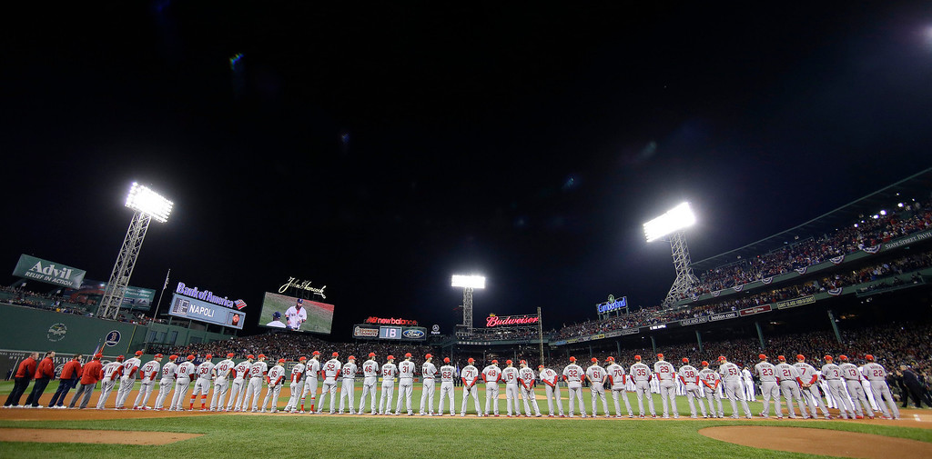 Description of . The St. Louis Cardinals line up along the third base line during introductions before Game 1 of baseball's World Series against the Boston Red Sox Wednesday, Oct. 23, 2013, in Boston. (AP Photo/Matt Slocum)
