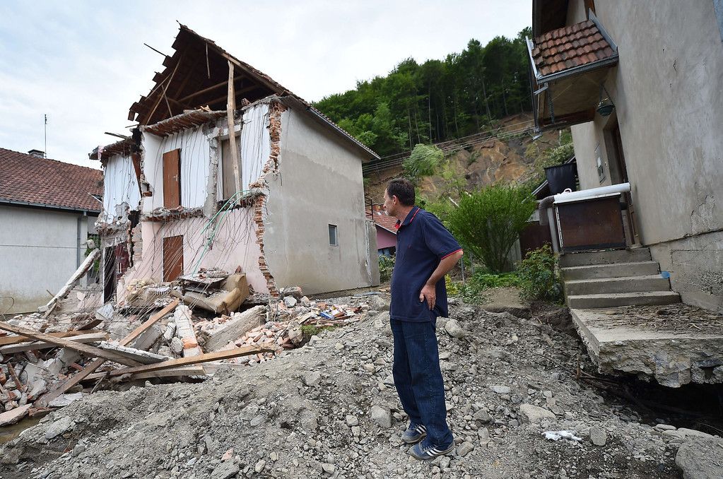 Description of . A man stands near his house damaged by flooding and landslide in Krupanj, some 130 kilometers south west of Belgrade, on May 20, 2014, after the western Serbian town was hit with floods and landslides, cutting it off for four days. Serbia declared three days of national mourning on May 20 as the death toll from the worst flood to hit the Balkans in living memory rose and health officials warned of a possible epidemic.    AFP PHOTO / ANDREJ ISAKOVIC/AFP/Getty Images