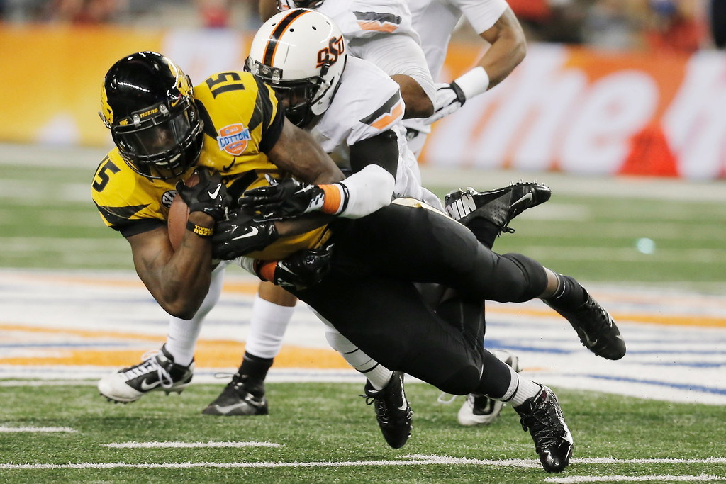 Description of . Missouri wide receiver Dorial Green-Beckham (15) is tackled by Oklahoma State safety Daytawion Lowe (8) during the second half of the Cotton Bowl NCAA college football game on Friday, Jan. 3, 2014, in Arlington, Texas. (AP Photo/Brandon Wade)