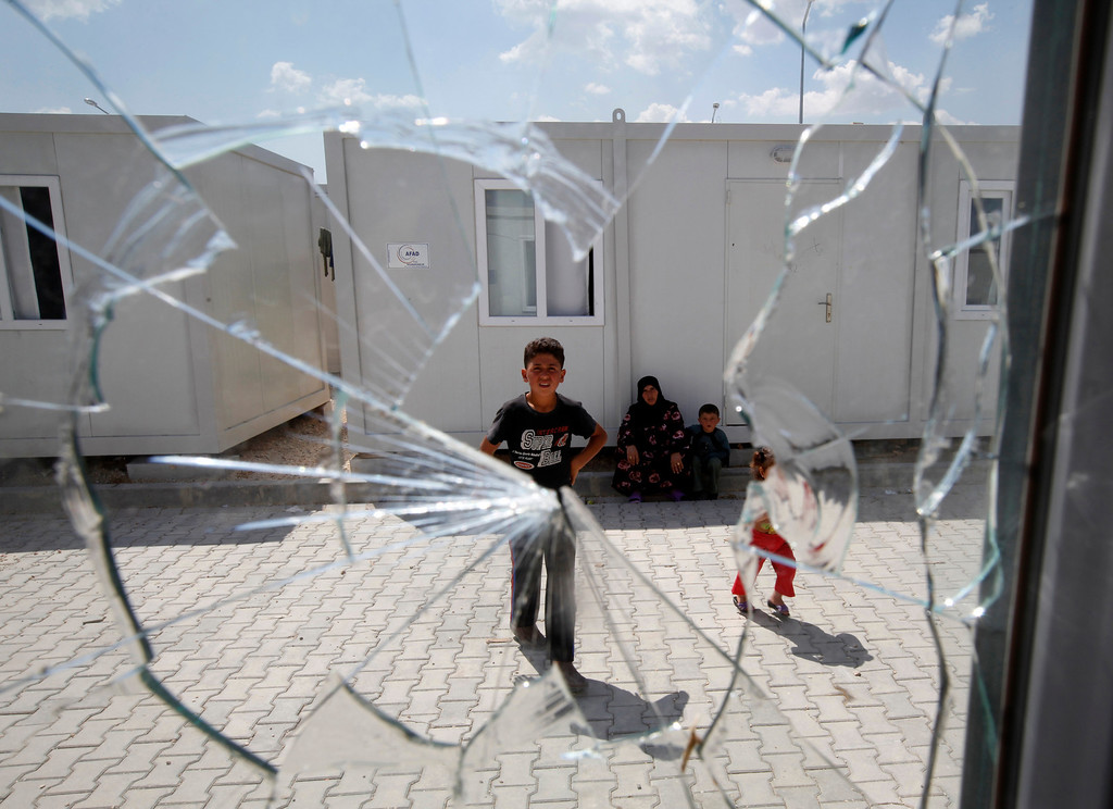 Description of . A window, broken by a stray bullet from clashes between the Syrian army and the rebels on Monday, is seen at a refugee camp named