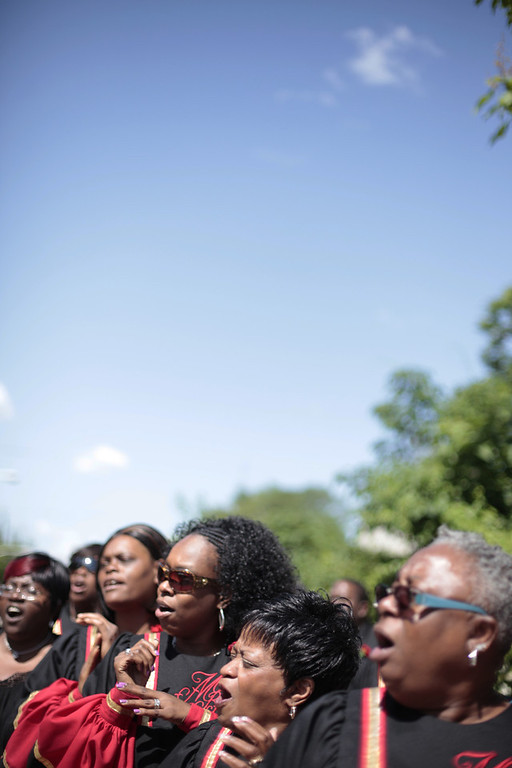 """Description of . Members of Mt. Olive Baptist Church Choir sing at the site of an abandoned home in the impoverished Mantua section Philadelphia on Saturday, May 31, 2014. The cultural and memorial project called """"Funeral for a Home"""" celebrated the dilapidated row house's colorful life before it was knocked down. Organizers from Temple University said it was an effort to commemorate neighborhood history in a city where about 600 houses are torn down each year and 25,000 others sit vacant. (AP Photo/Jessica Kourkounis)"""