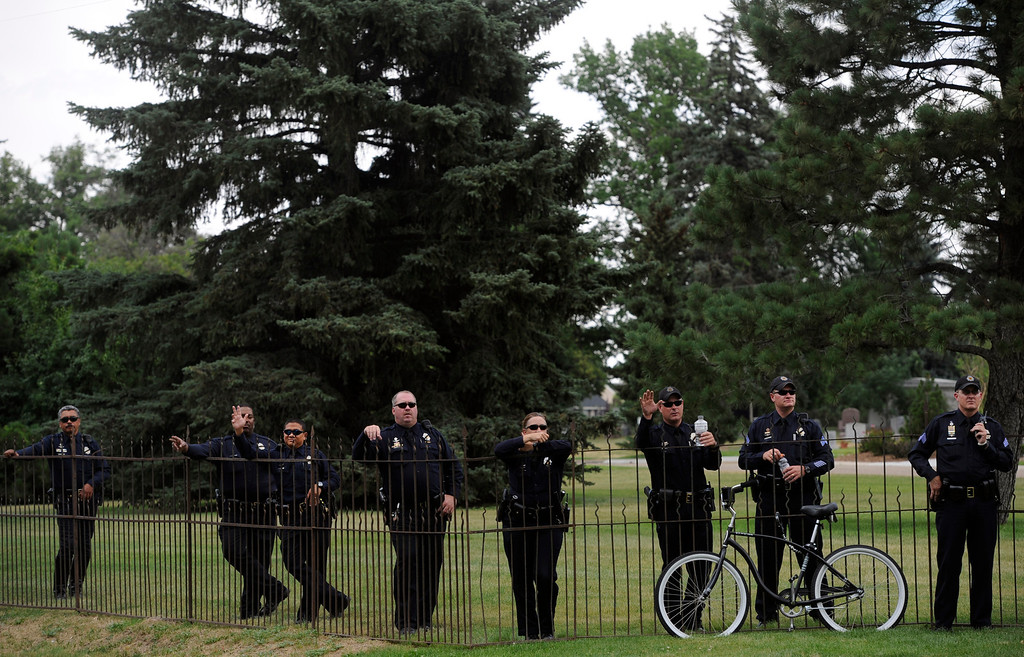 Description of . A small crowd of law enforcement officers gather on the lawn of the cemetery as they watch and wave to the long line of law enforcement vehicles entering the cemetery. Funeral services for Denver police officer Celena Hollis took place Saturday, June 30, 2012 at the First Church of the Nazarene followed by a procession to Fairmount Cemetery in Denver. Hollis was shot and killed in the line of duty. Kathryn Scott Osler, The Denver Post
