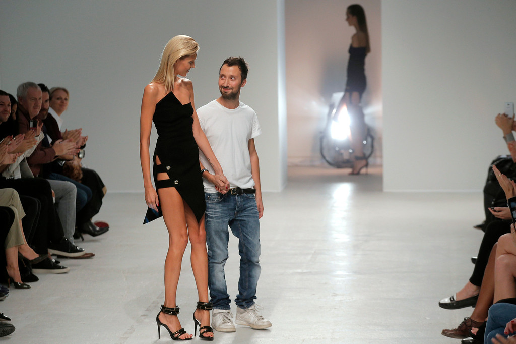 Description of . Italian fashion designer Anthony Vaccarello, centre right, holds the hand of a model as he acknowledges applause following the presentation of his ready-to-wear Spring/Summer 2014 fashion collection presented in Paris, Tuesday, Sept. 24, 2013. (AP Photo/Christophe Ena)