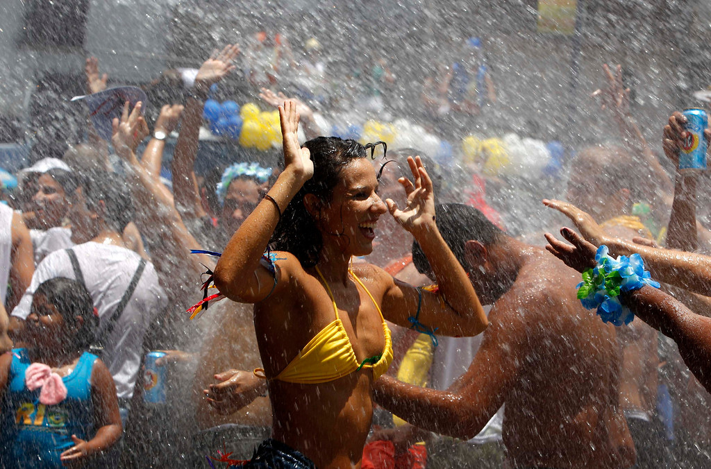 Description of . Water is sprinkled on revellers to help them cool off during an annual block party known as