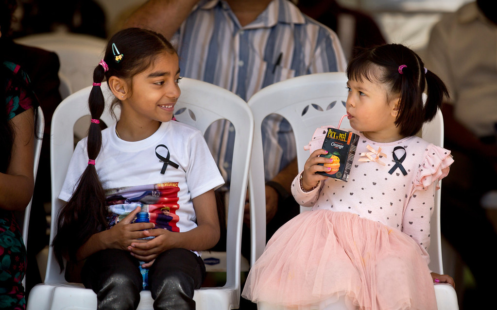 Description of . Stella, 3, right, whose mother Wendy Zhang lost her sister-in-law Zhou Jian in the Westgate attack, and an unidentified child relative of one of the victims, left, wear black ribbons as they attend a memorial service marking the one-month anniversary of the Sept. 21 Westgate Mall terrorist attack, in Karura Forest in Nairobi, Kenya Monday, Oct. 21, 2013. (AP Photo/Ben Curtis)
