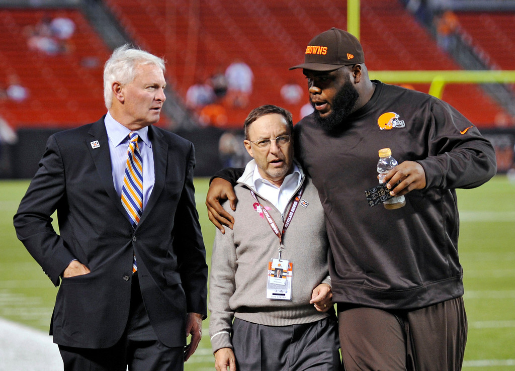 Description of . Cleveland Browns nose tackle Phillip Taylor, right, hugs team CEO Joe Banner as they walk with team owner Jimmy Haslam, left, before an NFL football game against the Buffalo Bills on Thursday, Oct. 3, 2013, in Cleveland. (AP Photo/David Richard)