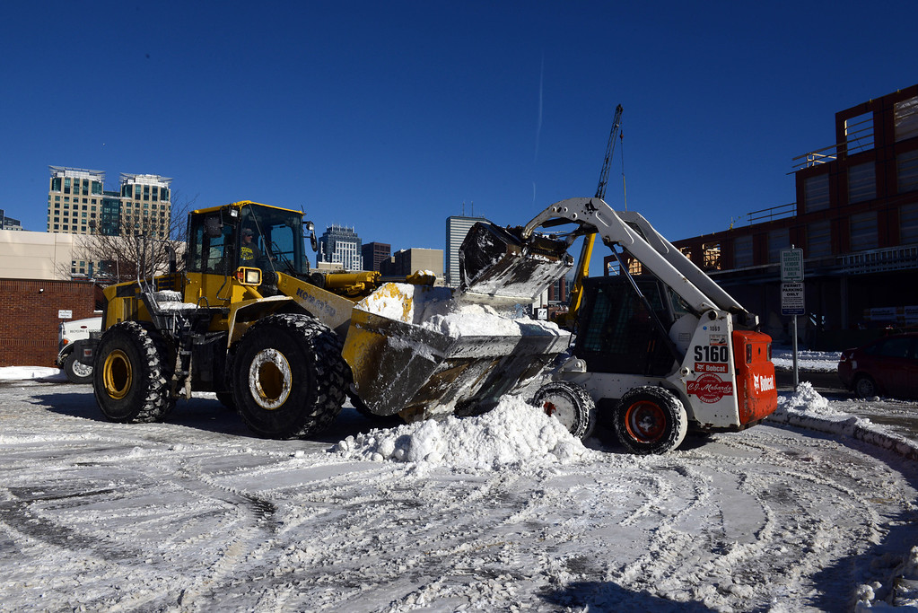 Description of . Plows clear snow from a lot in the South End after a two day winter storm January 4, 2014 in Boston, Massachusetts. The storm began mid day Thursday with heavy snows overnight into Friday bringing with it extreme cold. (Photo by Darren McCollester/Getty Images)