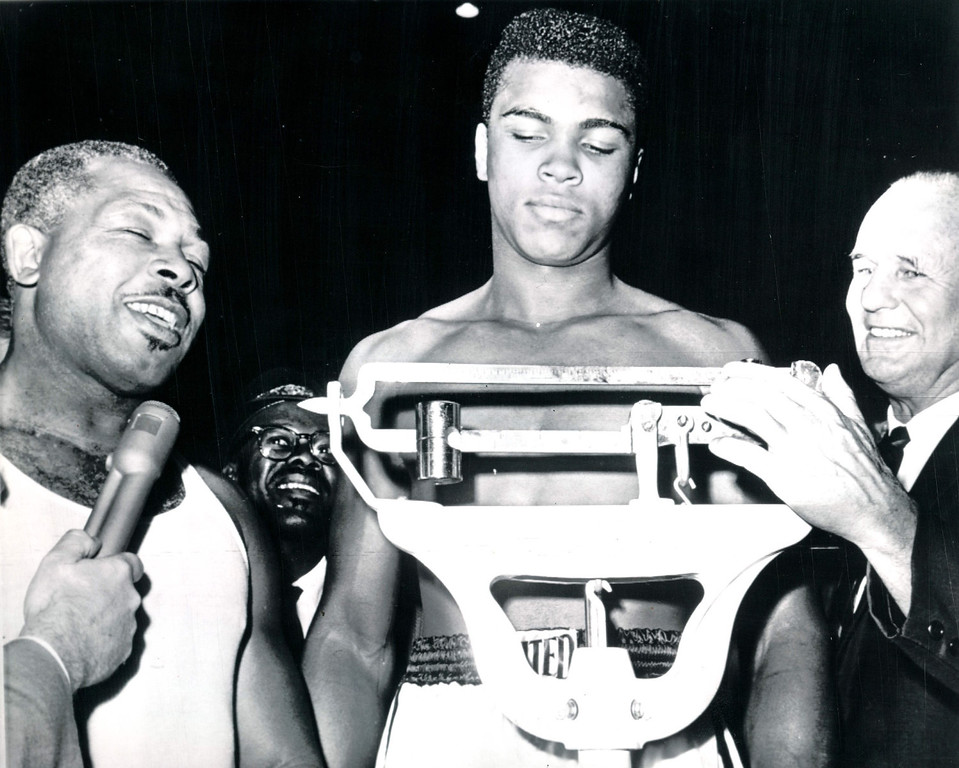 Description of . Cassius Clay weighs in a 204 pounds today for his 12-round heavyweight fight in Los Angeles tonight against Archie Moore, who came in at 197 pounds.  Adjusting scales is Clayton Frye, secretary of the California Athletic Commission. 1962. Credit: AP