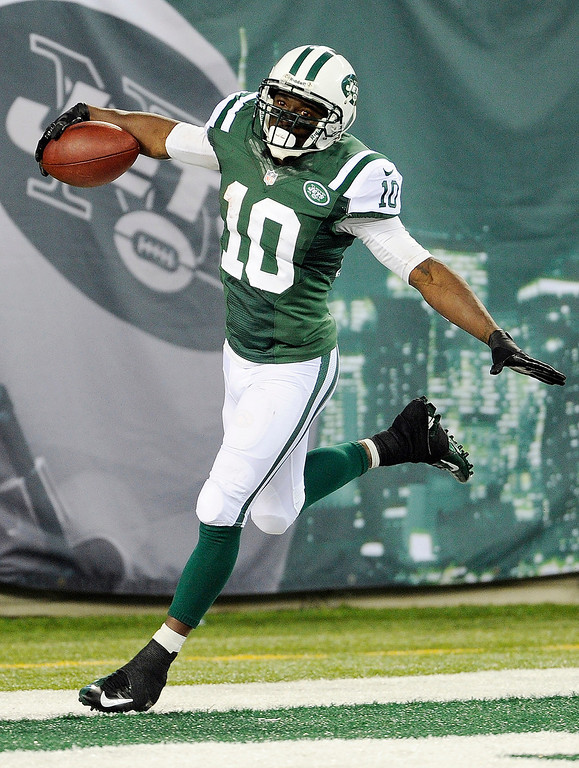 Description of . New York Jets wide receiver Santonio Holmes (10) celebrates after scoring a touchdown during the second half of an NFL football game against the Buffalo Bills Sunday, Sept. 22, 2013, in East Rutherford, N.J. (AP Photo/Bill Kostroun)