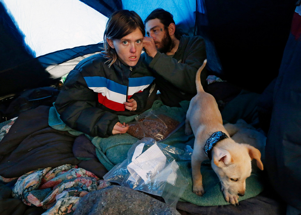 Description of . Sarah Davis, left, and John Davis, right, try to stay warm in their in their tent at a homeless encampment in Oklahoma City, Friday, Dec. 6, 2013. Despite the recent winter storm, they do not want to leave their tent to go to a shelter. Oklahoma Gov. Mary Fallin declared a state of emergency for all 77 counties Thursday as the first storm moved across the state. (AP Photo/Sue Ogrocki)