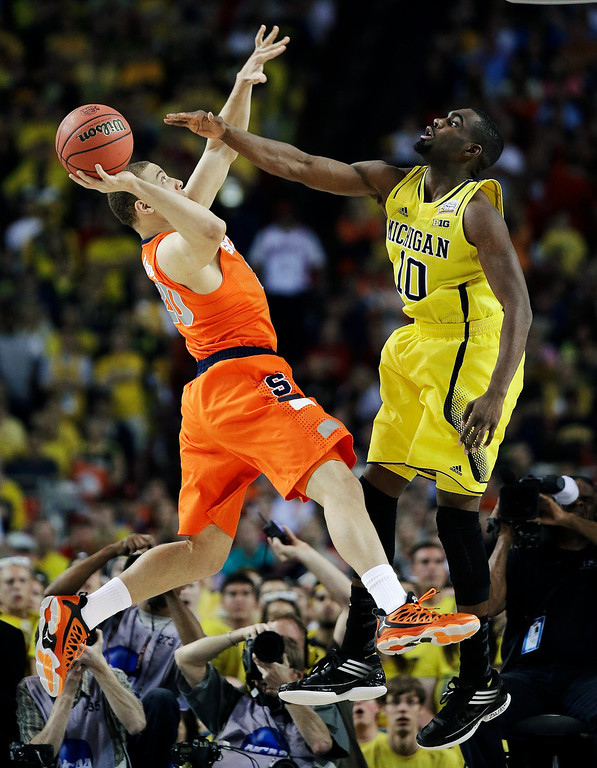 Description of . Syracuse's Brandon Triche (20) shoots against Michigan's Tim Hardaway Jr. (10) during the first half of an NCAA Final Four tournament college basketball semifinal game Saturday, April 6, 2013, in Atlanta. (AP Photo/David J. Phillip)