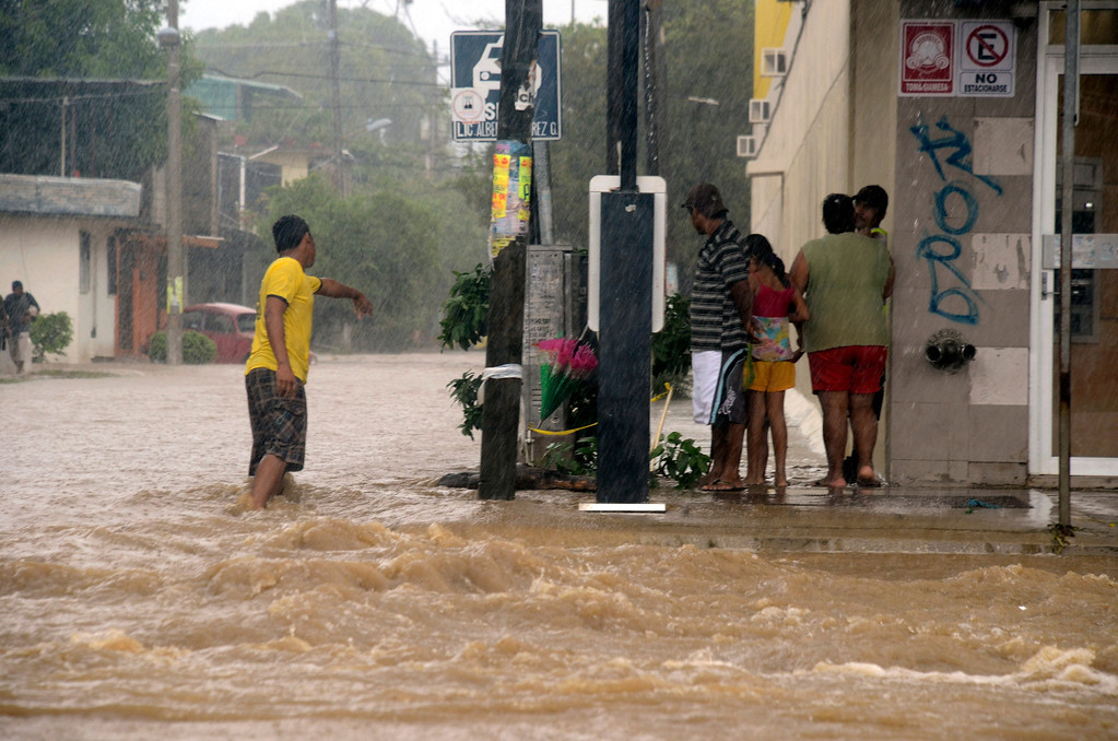 Description of . People stand at the corner of a flooded street caused by heavy rains brought by Tropical Storm Manuel in Acapulco, Mexico, Monday Sept. 16, 2013. Tropical Storm Ingrid and remnants of Tropical Storm Manuel drenched Mexico's Gulf and Pacific coasts, flooding towns and cities in a national emergency that federal authorities say has caused at least 34 deaths. (AP Photo/Bernandino Hernandez)