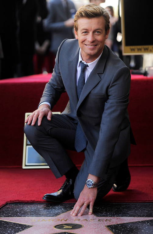 Description of . Australian actor Simon Baker poses next to his new star on the Hollywood Walk of Fame, on Thursday, Feb. 14, 2013 in Los Angeles. (Photo by Chris Pizzello/Invision/AP)