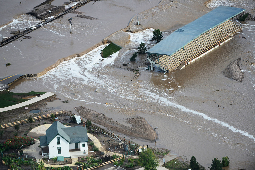 Description of . Flood waters cut in-between a house and a stadium in Loveland Colorado Saturday morning, September 14, 2013. (Photo By Andy Cross/The Denver Post)