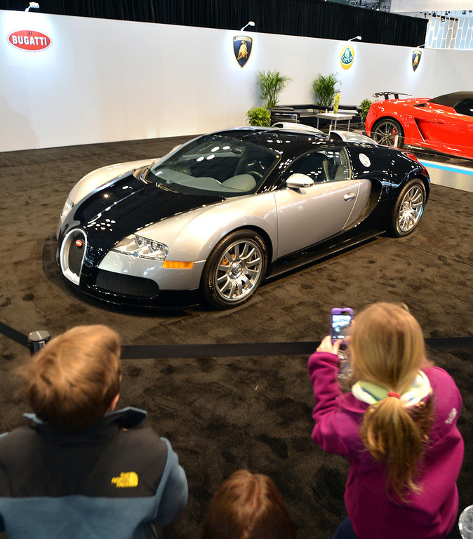 Description of . People view the Bugatti Veyron at a public preview of the New York International Auto Show on March 29, 2013 in New York. It has a price tag of $1.6 million. STAN HONDA/AFP/Getty Images