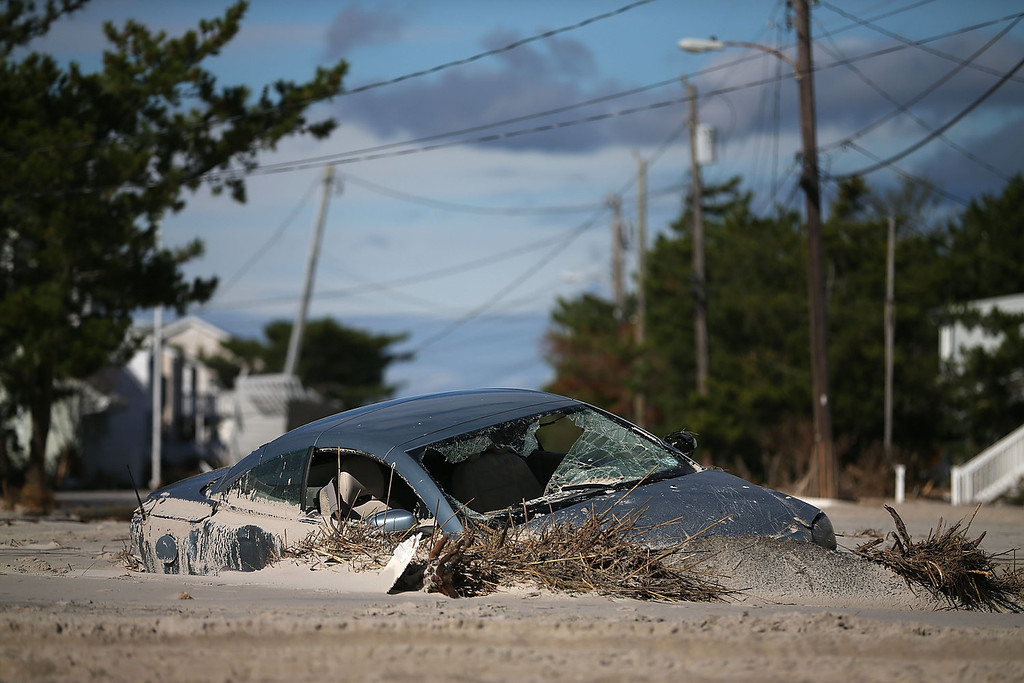 . A car is buried in sand that was washed in from Hurricane Sandy on October 31, 2012 in Long Beach Island, New Jersey. Earlier in the week Hurricane Sandy made landfall on New Jersey coastline bringing heavy winds and record floodwaters.  (Photo by Mark Wilson/Getty Images)