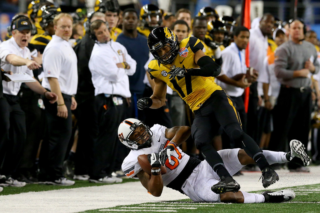 Description of . ARLINGTON, TX - JANUARY 03:  Tracy Moore #87 of the Oklahoma State Cowboys makes a catch against Matt White #17 of the Missouri Tigers in the second half during the AT&T Cotton Bowl on January 3, 2014 in Arlington, Texas.  (Photo by Ronald Martinez/Getty Images)