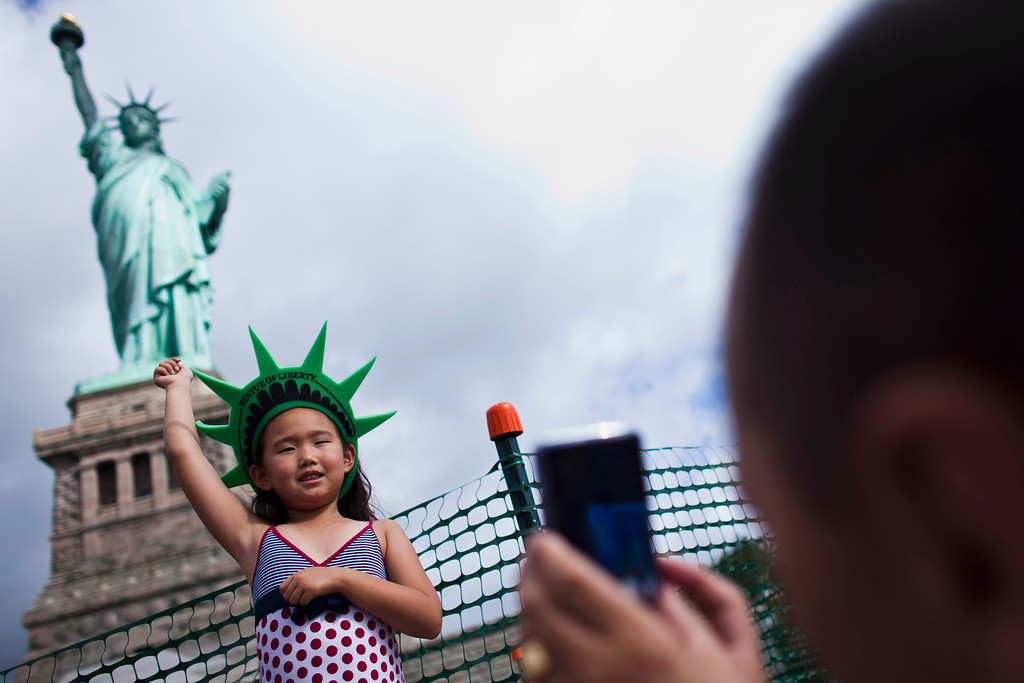 Description of . A girl poses for her father as they visit the Statue of Liberty and Liberty Island during its reopening to the public in New York, July 4, 2013. Under steamy summer skies, tourists in New York flocked to ferries headed for the Statue of Liberty, re-opening with an Independence Day ceremony after closing in October as Superstorm Sandy approached.  REUTERS/Eduardo Munoz