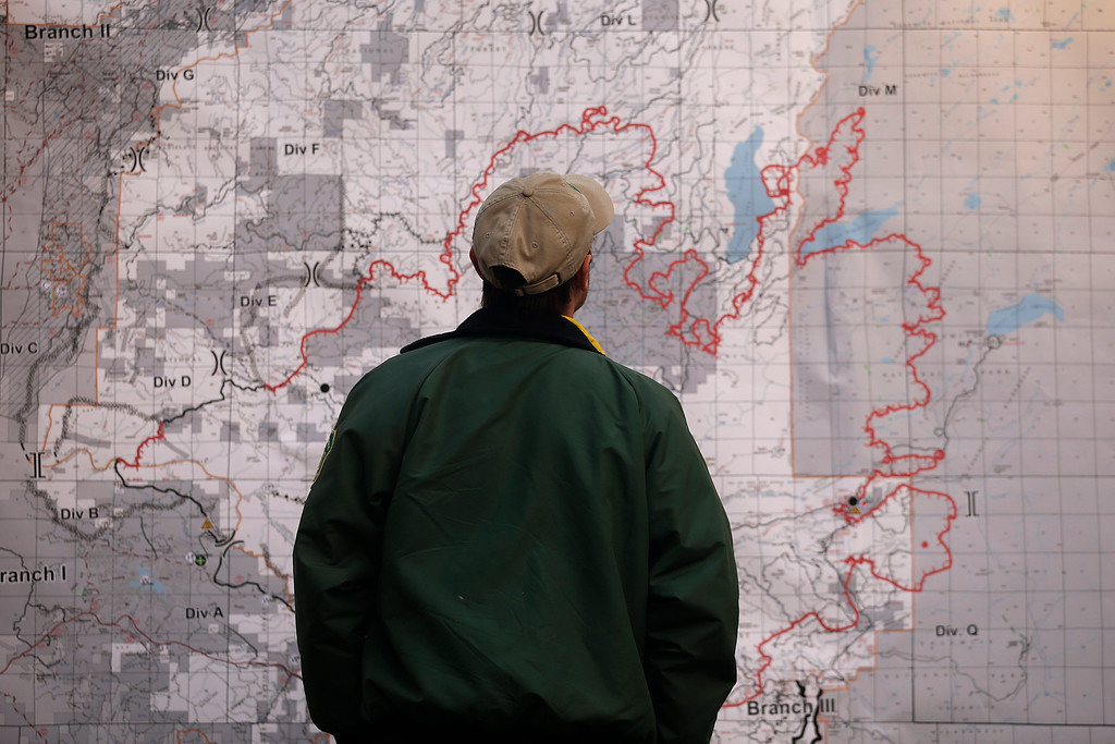 Description of . A firefighter looks at the Rim Fire incident report map posted at the command post near Yosemite National Park, Calif., on Monday, Aug. 26, 2013.  (AP Photo/Jae C. Hong)