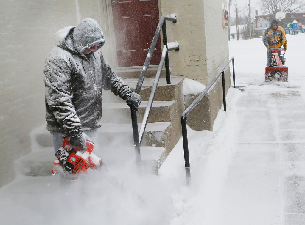 Description of . Tim Johnson, left, and Michael Bennett clear the snow from the sidewalks and steps around St. James Lutheran Church Thursday, jan. 2, 2014, in Lafayette, Ind. North central Indiana was blanketed on Thursday by several inches of snow. (AP Photo/Journal & Courier, John Terhune)
