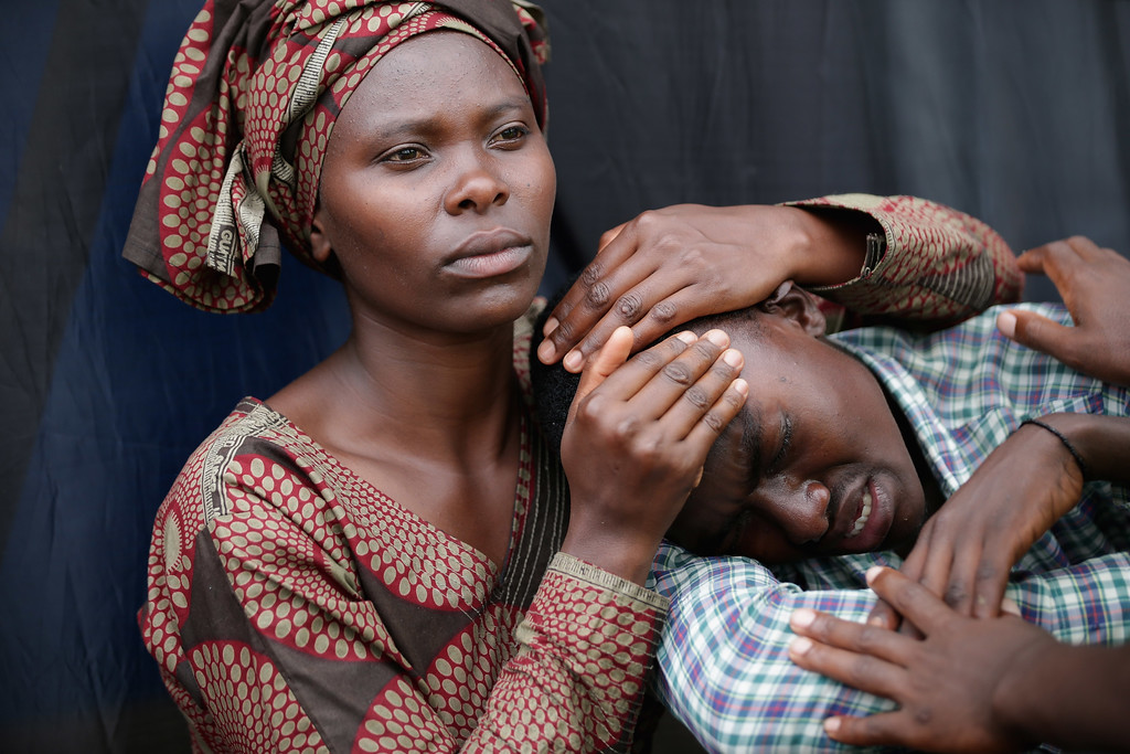Description of . A woman consoles Bizimana Emmanuel, 22, during the 20th anniversary commemoration of the 1994 genocide at Amahoro Stadium April 7, 2014 in Kigali, Rwanda. Thousands of Rwandans and global leaders, past and present, joined together at the stadium to remember the country's 1994 genocide, when more than 800,000 ethnic Tutsi and moderate Hutus were slaughtered over a 100 day period.  (Photo by Chip Somodevilla/Getty Images)