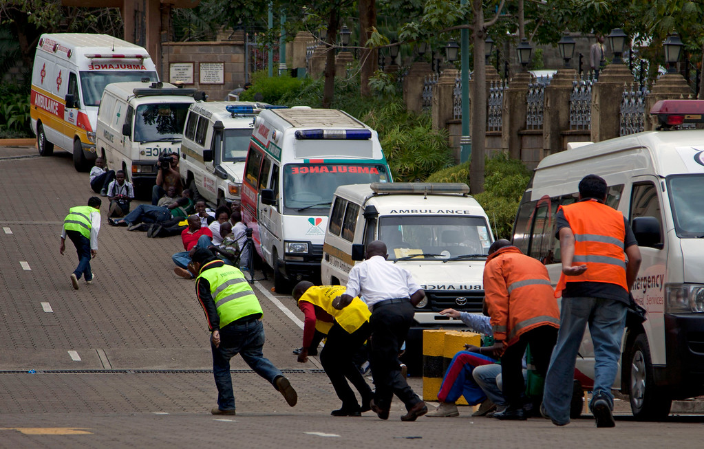 Description of . Paramedics run beside parked ambulances outside the Westgate Mall in Nairobi after heavy shooting started for the third time since the morning Monday, Sept. 23, 2013. (AP Photo/Sayyid Azim)